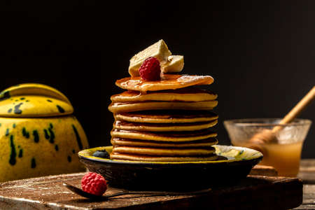 Homemade Stack of Pancakes with Butter and Syrup for Breakfast on wooden dark background table. Copy space for your text.