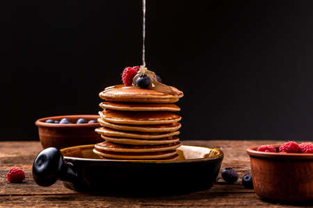 Pouring honey on stack of tasty pancakes on wooden table. homemade classic american pancakes with fresh berry and honey.