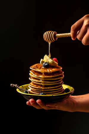 Woman pouring honey on tasty pancakes with berries on table, closeup. cooking by chef hand on dark background.