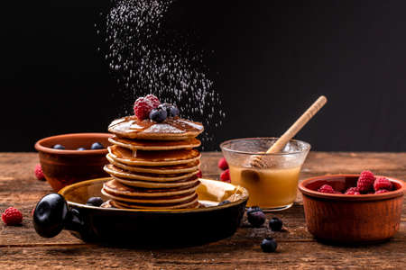 Stack of pancakes with sugar powder splashes on dark background table. homemade classic american pancakes with fresh berry and honey. Copy space for your text.