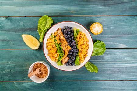 Diet menu. Healthy Green salad with chicken breast, corn, lemon, mustard and blueberries. Top view.