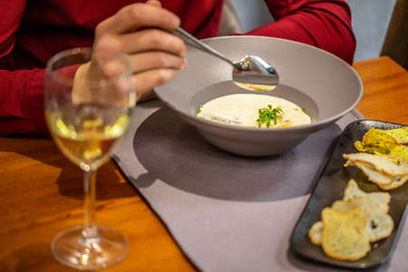 cheese soup with turkey fillet .A glass of white wine. restaurant food. author menu. Delicious homemade food. Croutons on the White Boards.
