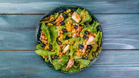 Fresh Tasty blueberries salad with chicken fillet, green vegetables and mustard. healthy food. banner, catering menu recipe place for text, top view.
