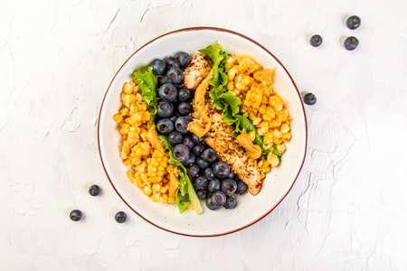 Ketogenic diet breakfast. Chicken salad with corn, lemon, mustard blueberries. Keto paleo lunch. Top view.