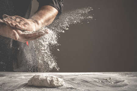 Photo of flour and men hands with flour splash. Cooking bread. Kneading the Dough. Isolated on dark background. Empty space for text