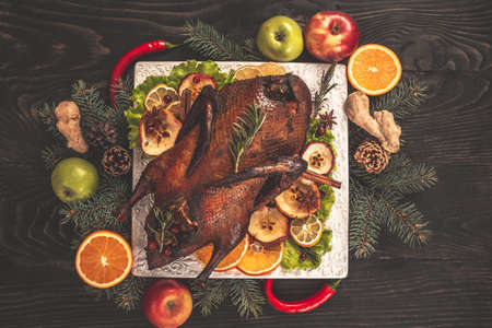 Roast Christmas duck with oranges and apples on rustic wooden table, ndependence Day of the United States, Day of Grace, Christmas. Culinary recipes for the holiday