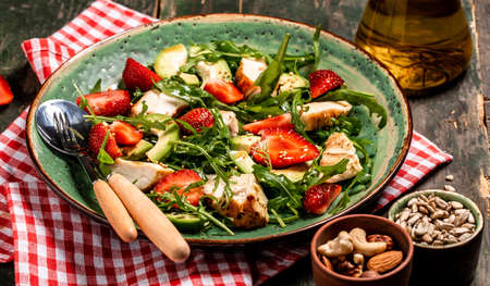 Fresh strawberry salad with arugula, chicken, avocado and strawberries. Plate with a keto diet food. Top view, Food recipe background. Close up