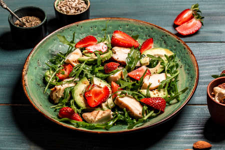 Fresh strawberry salad with arugula, chicken, avocado and strawberries. Plate with a keto diet food. Top view