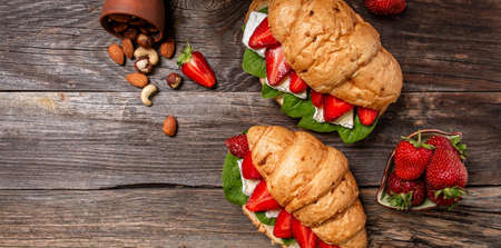 Breakfast, business lunch, sandwiches Croissant with strawberries and soft cheese with mold brie camembert on wooden background. Long banner format. space for text