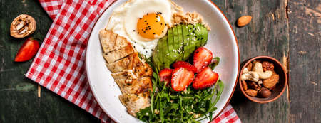 Buddha bowl with chicken, arugula and strawberries. keto diet food recipe background. Long banner format, top view