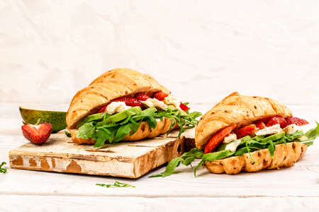 Food recipe background. Close up Breakfast, business lunch, sandwiches Croissant with strawberries and soft cheese with mold brie camembert. banner menu recipe top view