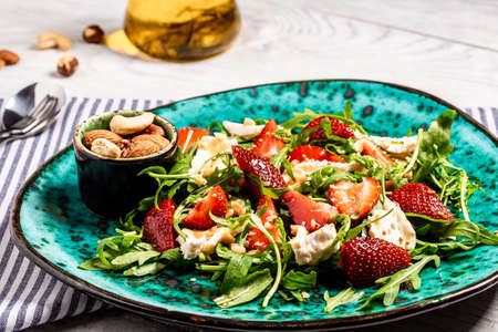 Close up salad with arugula, strawberries and cheese brie, camembert. Healthy food diet food concept. recipe background