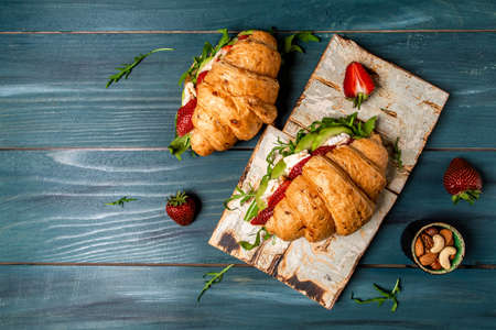 Breakfast, business lunch, sandwiches Croissant with strawberries and soft cheese with mold brie camembert on wooden background. banner menu recipe top view