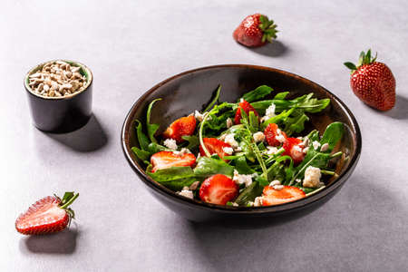 Healthy food, salad of fresh strawberries, arugula, ricotta and seeds on a bowl. Vegan food. Flat lay. Top view