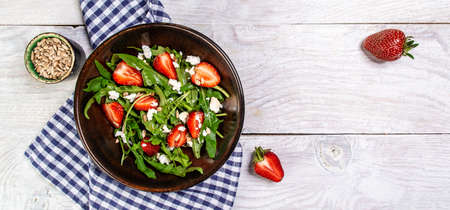 Diet menu. Healthy salad of fresh strawberries, arugula, ricotta and seeds on a bowl. Vegan food. Flat lay. Banner. Top view