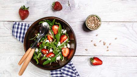 Dietary menu. Healthy vegan salad of vegetables strawberries, arugula, ricotta and seeds in a bowl. Flat lay. Top view 写真素材
