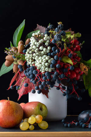 Autumn still life with fruits and a bouquet of berries and leaves on a dark background.