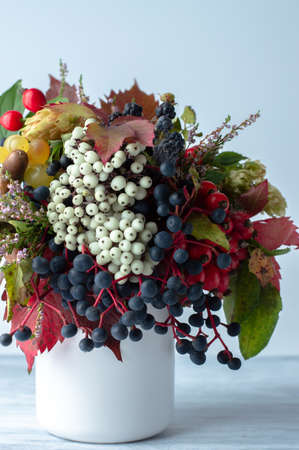 Autumn bouquet of berries, fruits and leaves in a ceramic light vase on a light background in a sunny day.