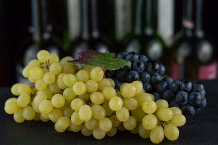 In the foreground is a bunch of white and blue grapes, in the background there are indistinct wine bottles.