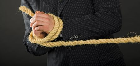 mislead: businessman hands with rope isolated on the black Stock Photo