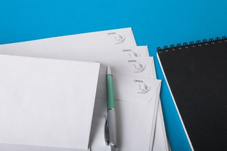 writing materials. evelops pen and notebook isolated on blue photo