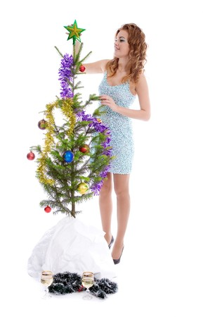 Elegant beautiful blond girl decorating christmas tree photo
