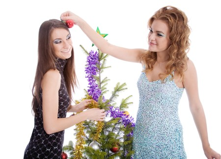 Two  young girls playing near fir tree photo