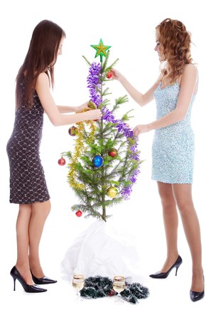 Two girls decorating fir tree with toys photo