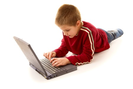 Child lying near computer and typing something photo