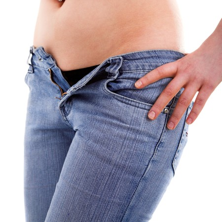 Young girl with piersing unzipping her jeans photo