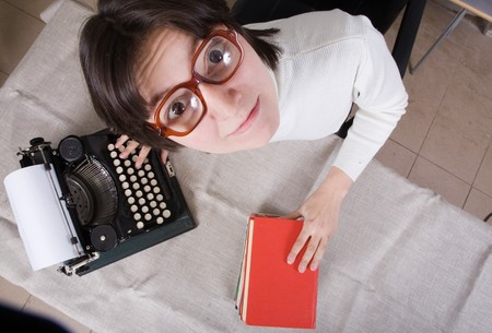 young woman in eyeglasses with old typewriter photo