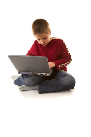 Child sitting near computer and typing something photo