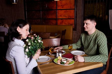 man givig flowers to the woman at restauran photo
