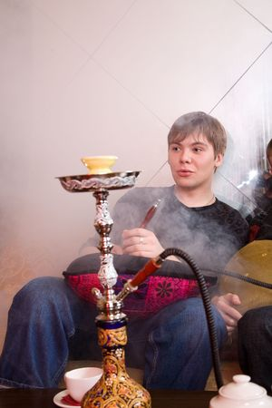 pipe smoking: young man smoking hookah in the room Stock Photo