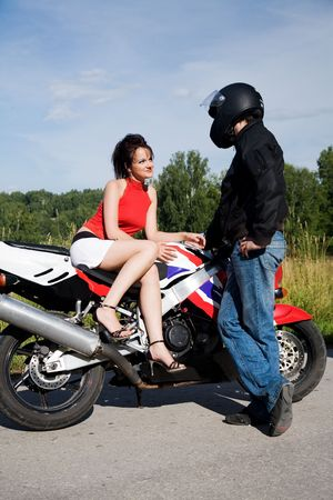 young beauty couple with motorbike on the road photo