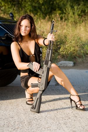young beauty girl with gun and car photo