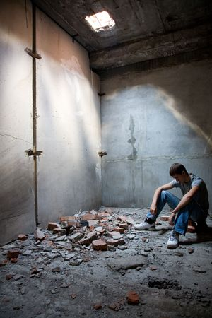 earthquake crack: young unhappy man in the rusty building