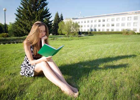 young girl with book  in the spring park photo