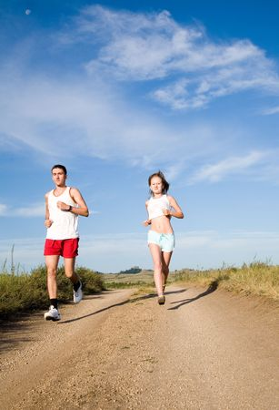 young beauty couple running on the summer road photo
