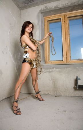 young beauty girl with rope against window photo