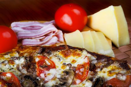 pizza with red tomato cheese and  pork photo