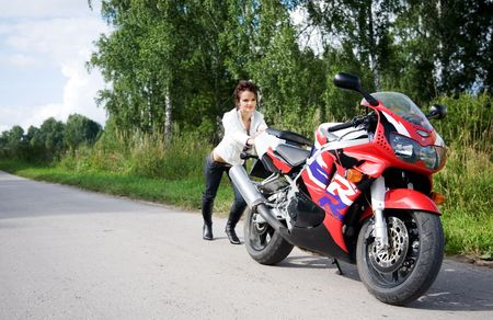 young beauty girl with motorbike on the road photo