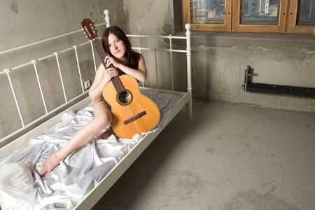 penury: beauty girl with guitar on the bed