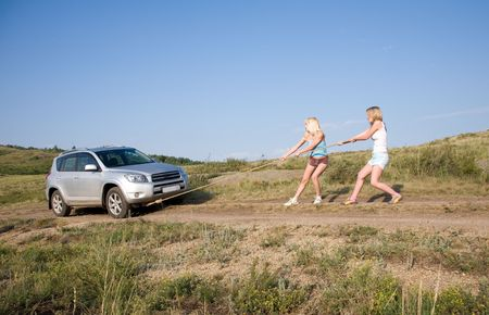 two young beauty girl tugging car on the solitary road photo