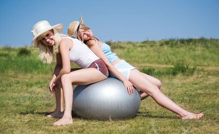 two young beauty girls sitting on the big ball photo