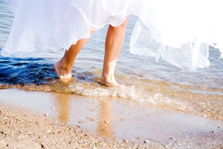feet in water: happy bride on the beach
