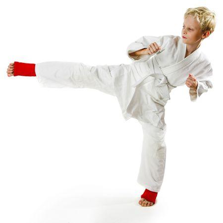 Karate boy exercising on white background photo
