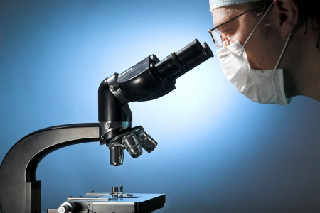 scientific experiment: Closeup of a male researcher looking through microscope
