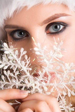 Young beauty Santa with snowflake in hands photo