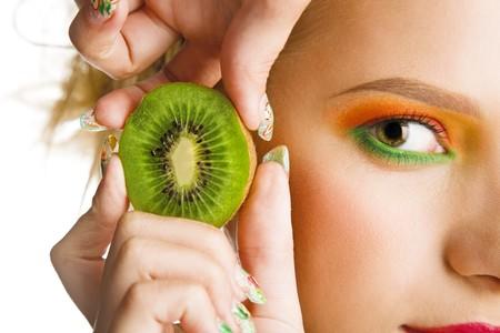 piel: mujer hermosa celebraci�n de kiwi fresca aislado en blanco